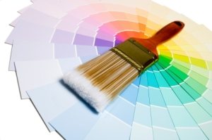 A paint brush over a wheel of colorful paint swatches